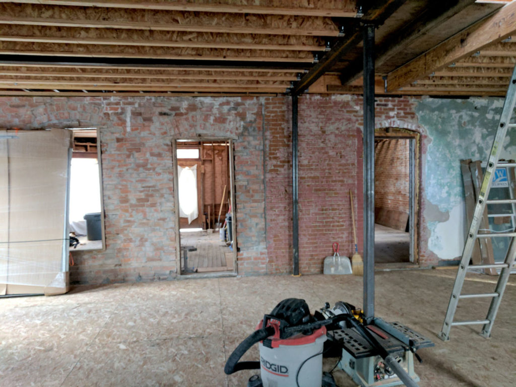 The unfinished dining room with the original brick walls.
