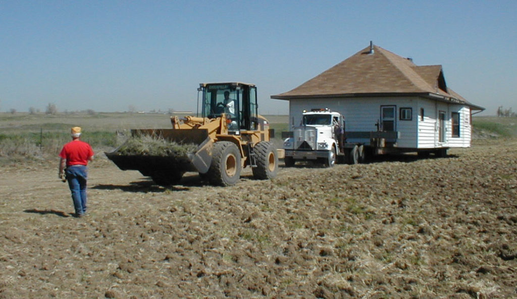 Contractor Bill McKee uses his loader to help mover Tom Whitlock pull the Bateman House across Chuck Waneka's field.