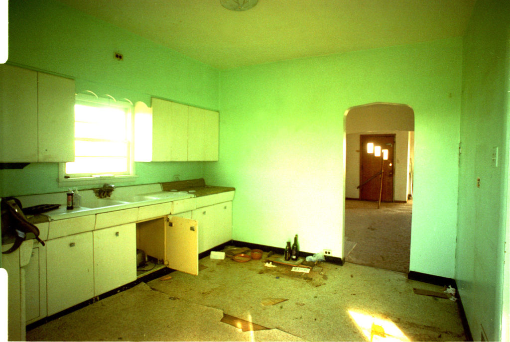 The large, lime-green kitchen of the Thomas House was updated in the 1960s, but by 1995 showed its age. The arched doorway was removed and the opening widened to give the first floor an open feel.