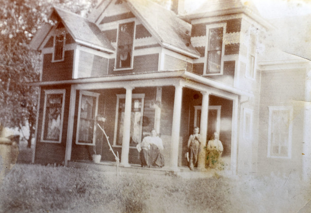 Anna Waneka Thomas is on the front porch of her house, about 1905 to 1907. Her son, either Richard or Daniel Thomas is standing, and her second husband Frank Greenlee is seated. Photo from the Doug Conarroe collection, donated by Lorraine (Thomas) Bateman.