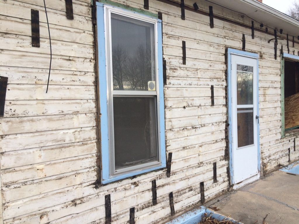 With the asbestos siding removed, the drop siding is revealed.
